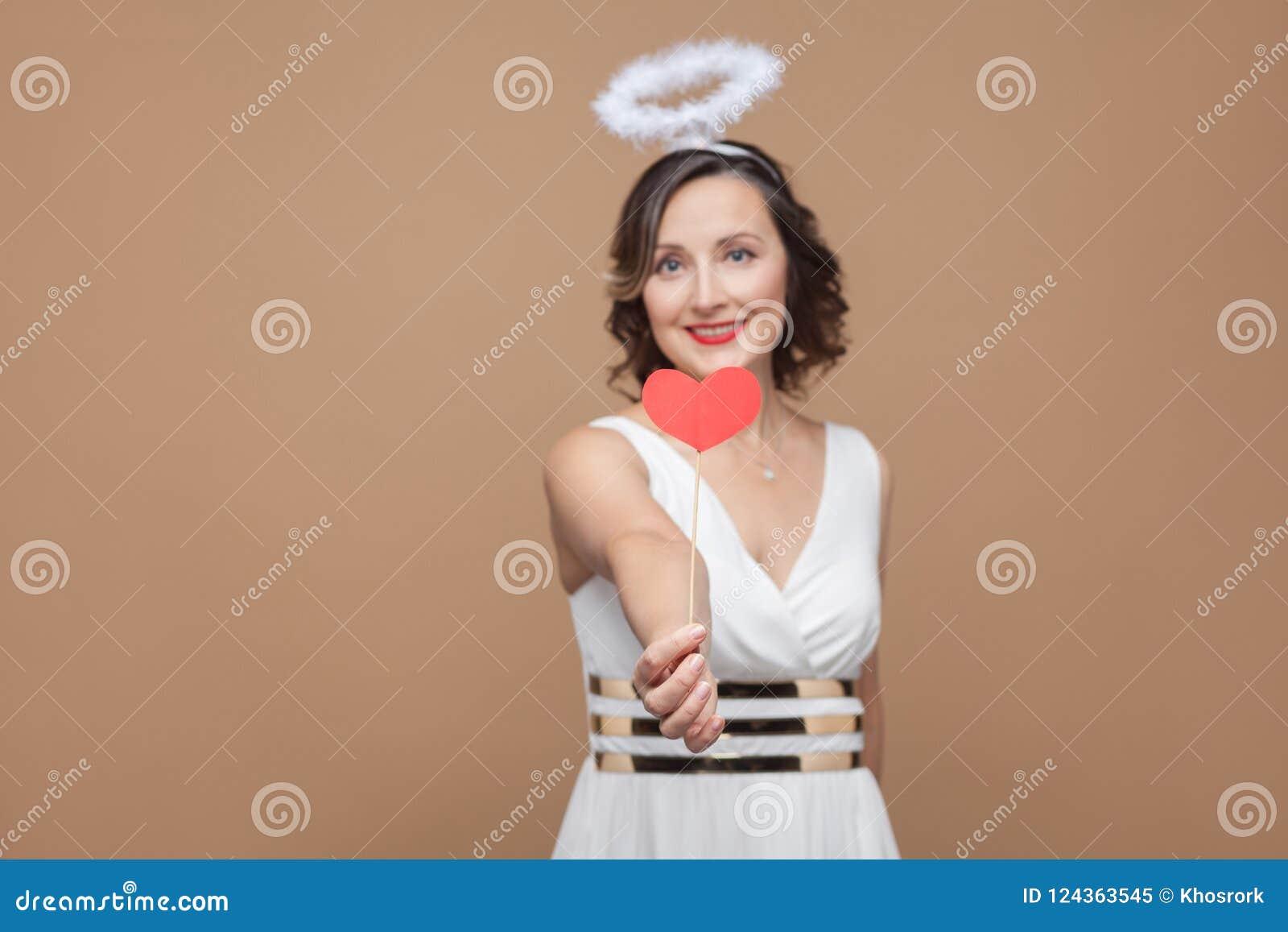 Il mezzo ha invecchiato la donna castana di angelo in vestito bianco con nimbus sulla t