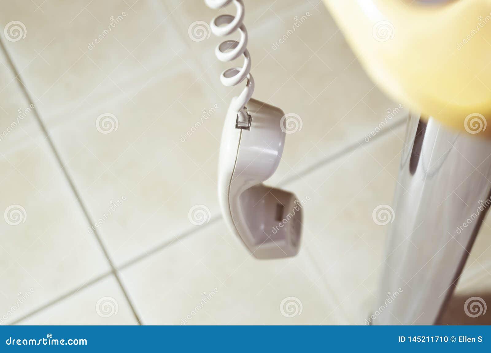 Il microtelefono del telefono metallico sta appendendo sul cavo