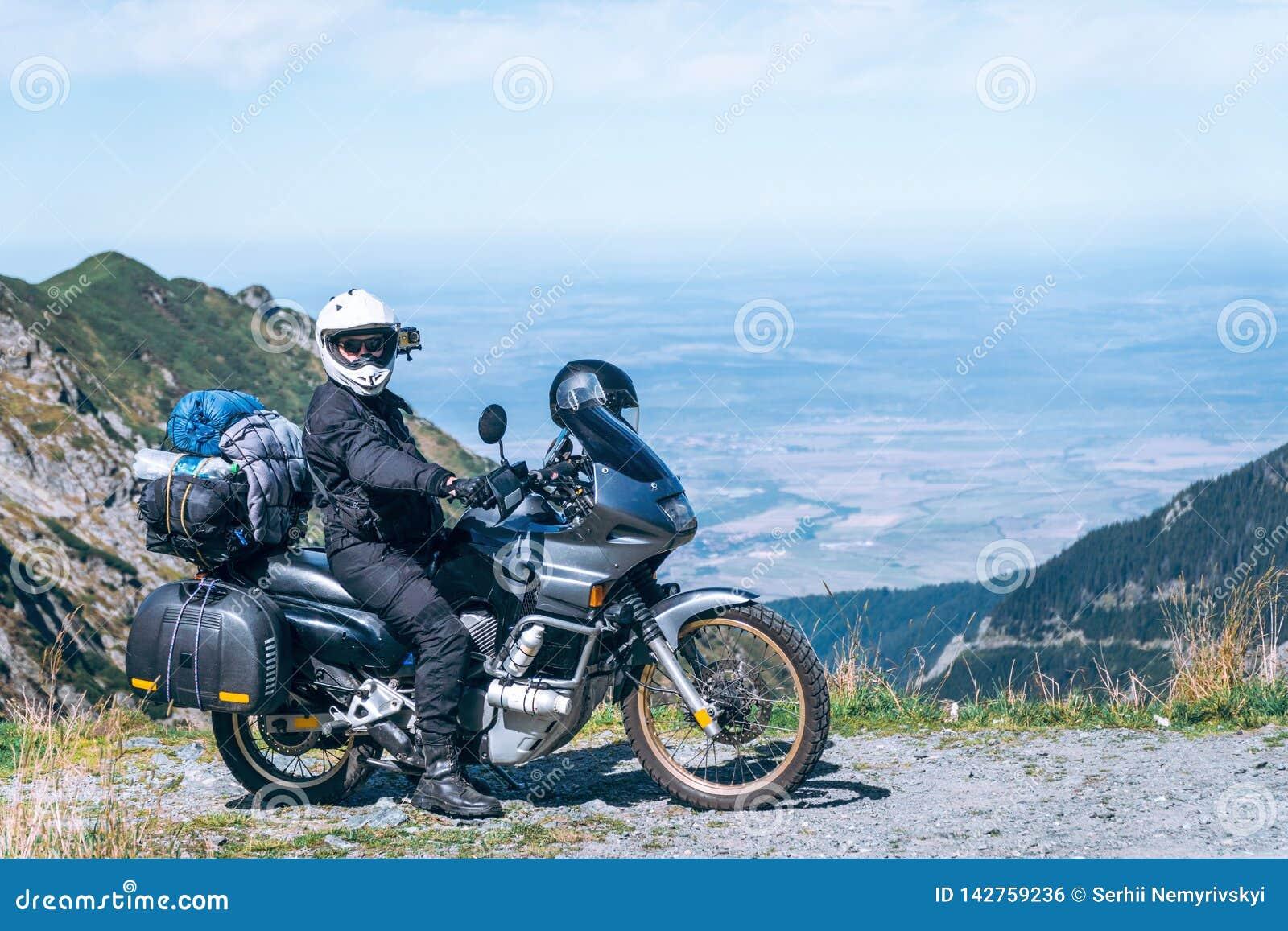 Il motociclista sta sedendosi sul suo motociclo di avventura, la montagna superiore nel fondo, enduro, fuori dalla strada, bella