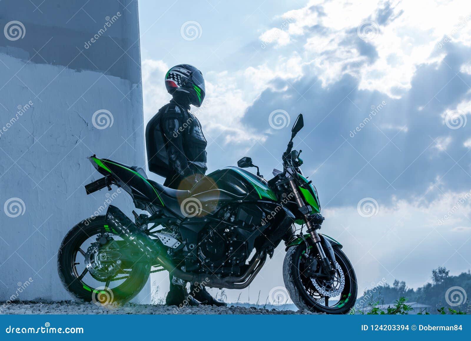Il motociclista in un casco ed in un vestito protettivo sta sotto il ponte