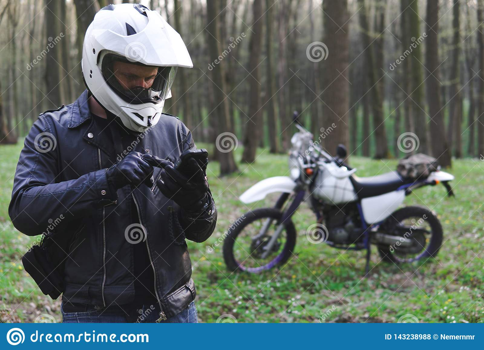 Il motociclo classico di enduro fuori dalla strada nella foresta di primavera, uomo in un bomber alla moda utilizza uno smartphon