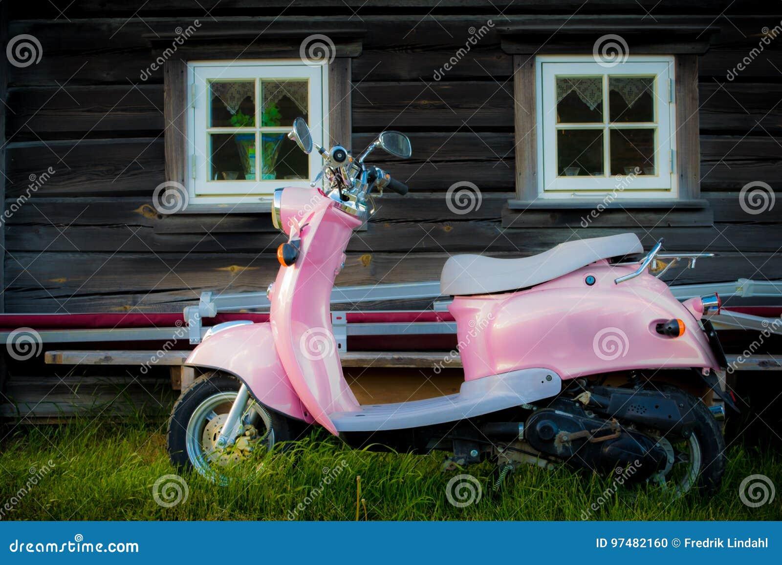Il motorino rosa sta parcheggiato vicino a vecchia costruzione di legno