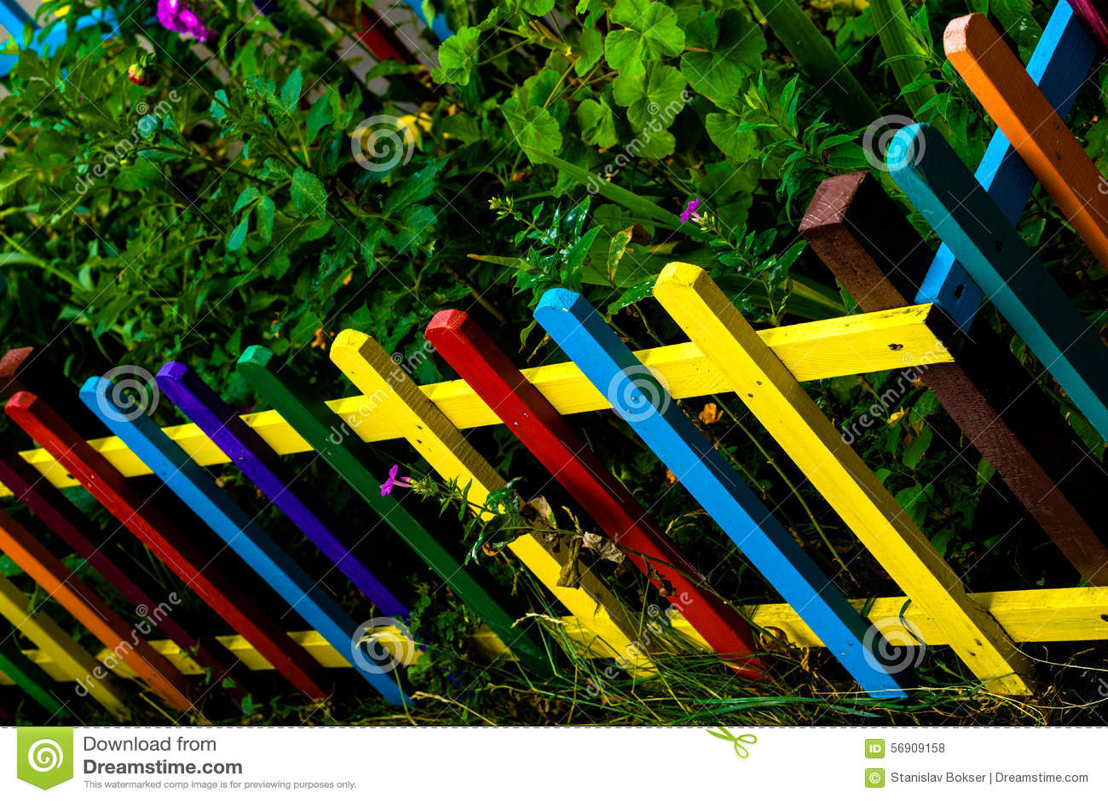 Il multi arcobaleno colorato di legno recinta il giardino fotografia
