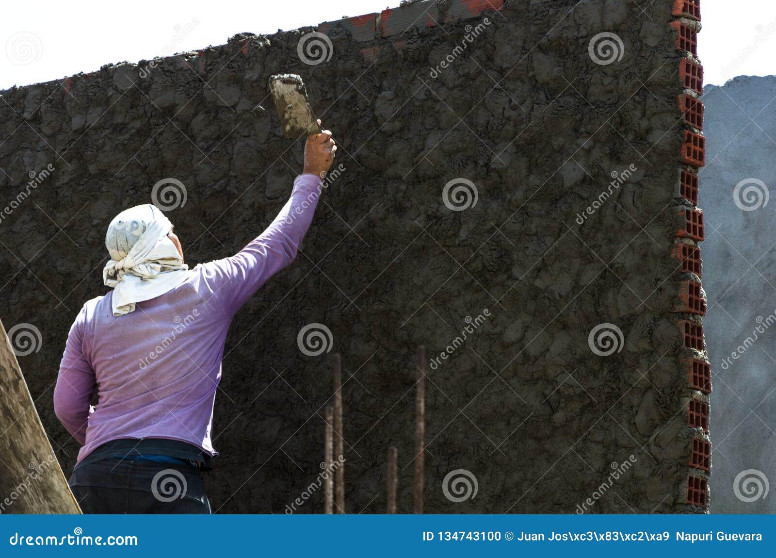 Il muratore - intonacando e lisciando muro di cemento con cemento da una cazzuola d acciaio - spatola allinea