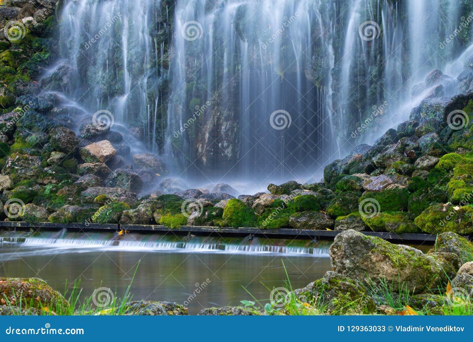 Il muschio verde ha coperto le pietre in cascate