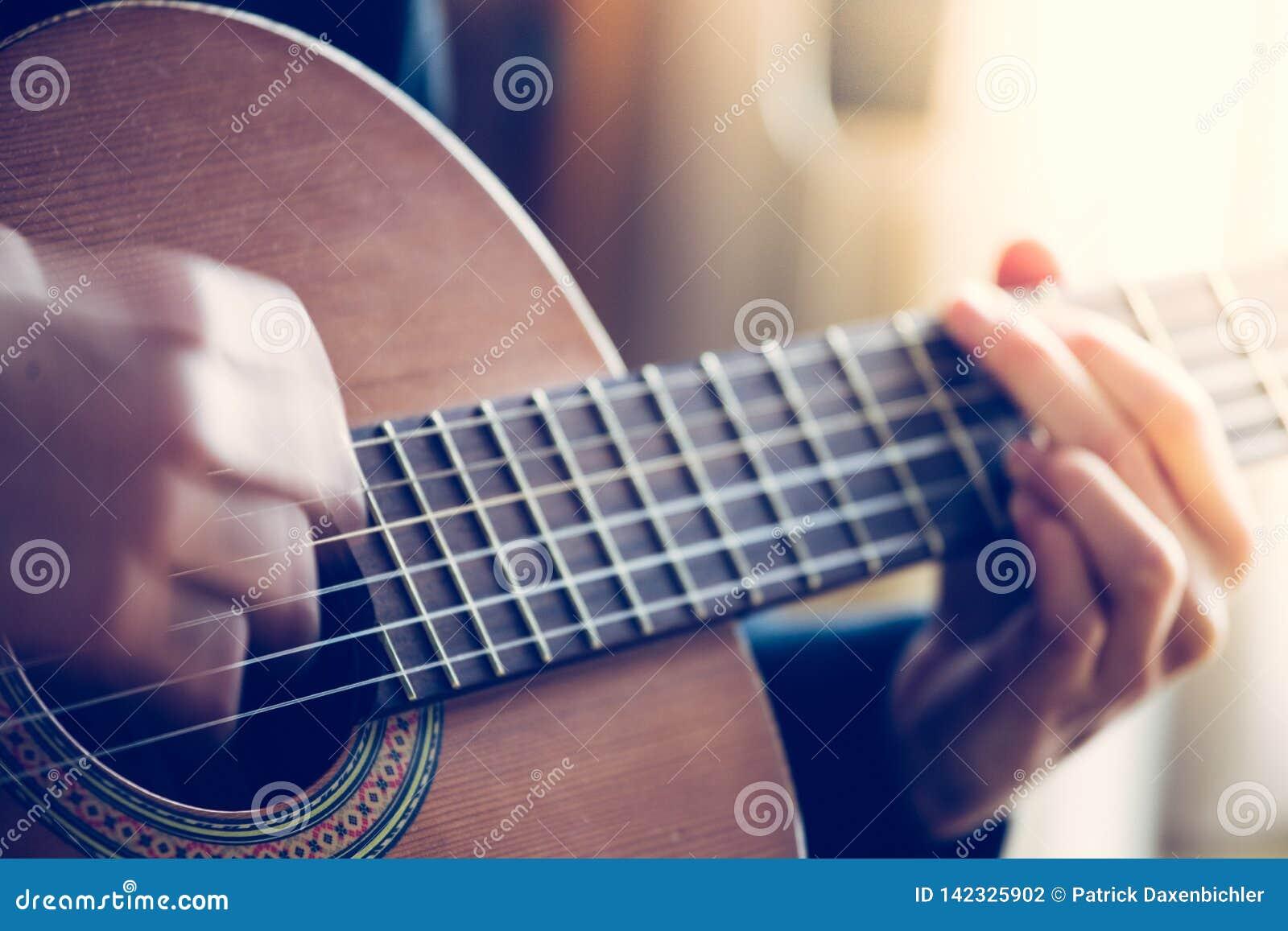 Il musicista sta giocando una chitarra, un fretboard e le dita classici