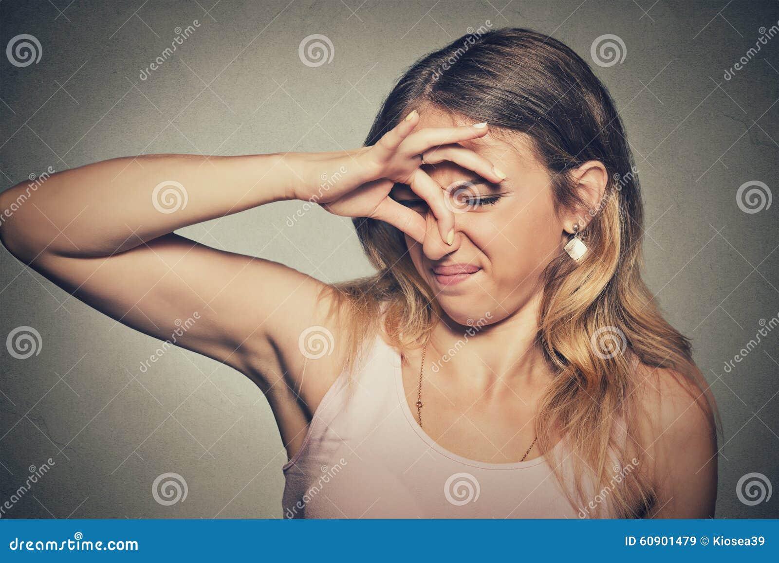 Il naso di pizzichi della donna con gli sguardi delle dita con repulsione qualcosa puzza il cattivo odore