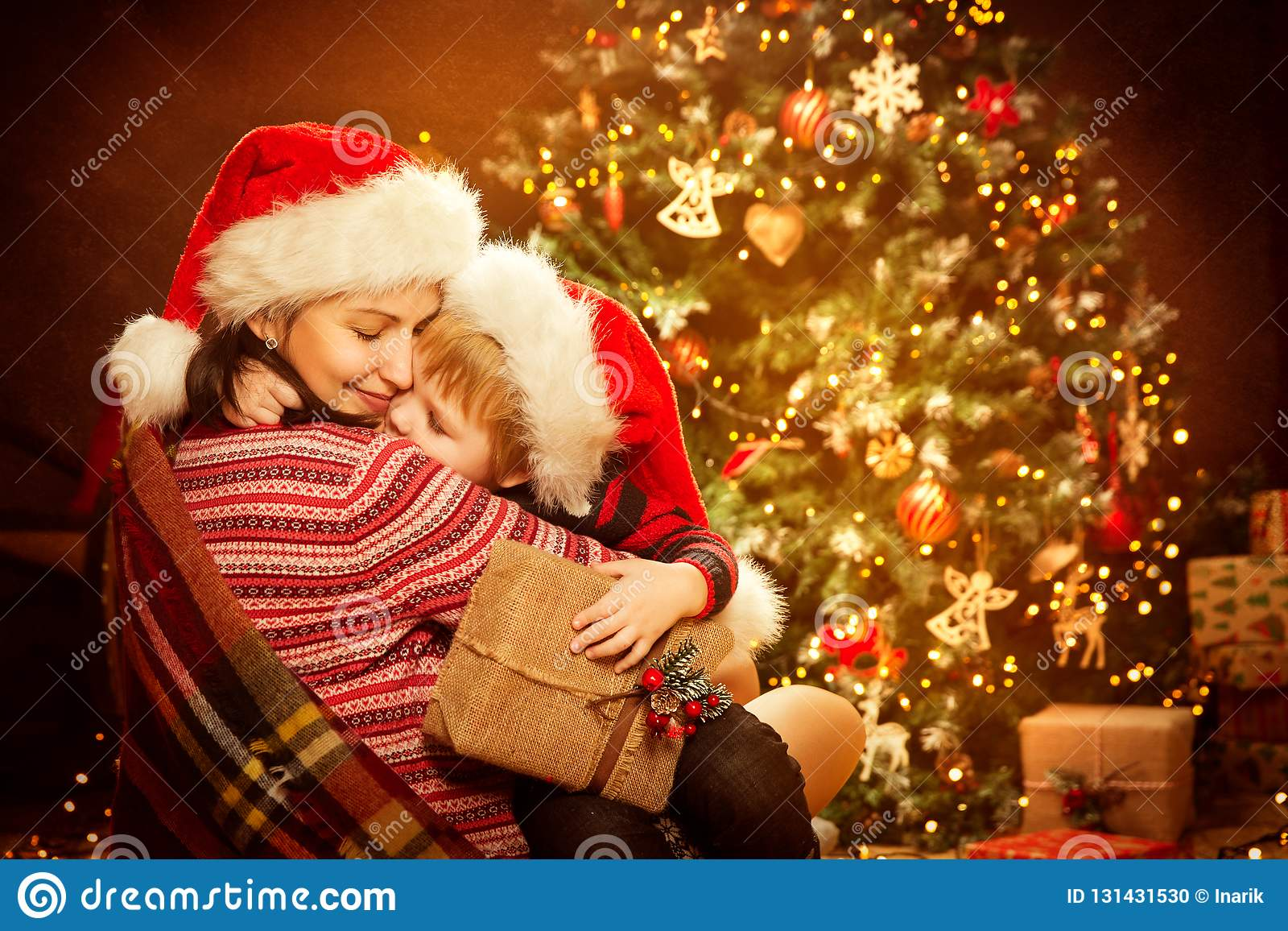Il Natale famiglia e l albero di natale, madre felice danno il regalo attuale del nuovo anno del bambino del bambino