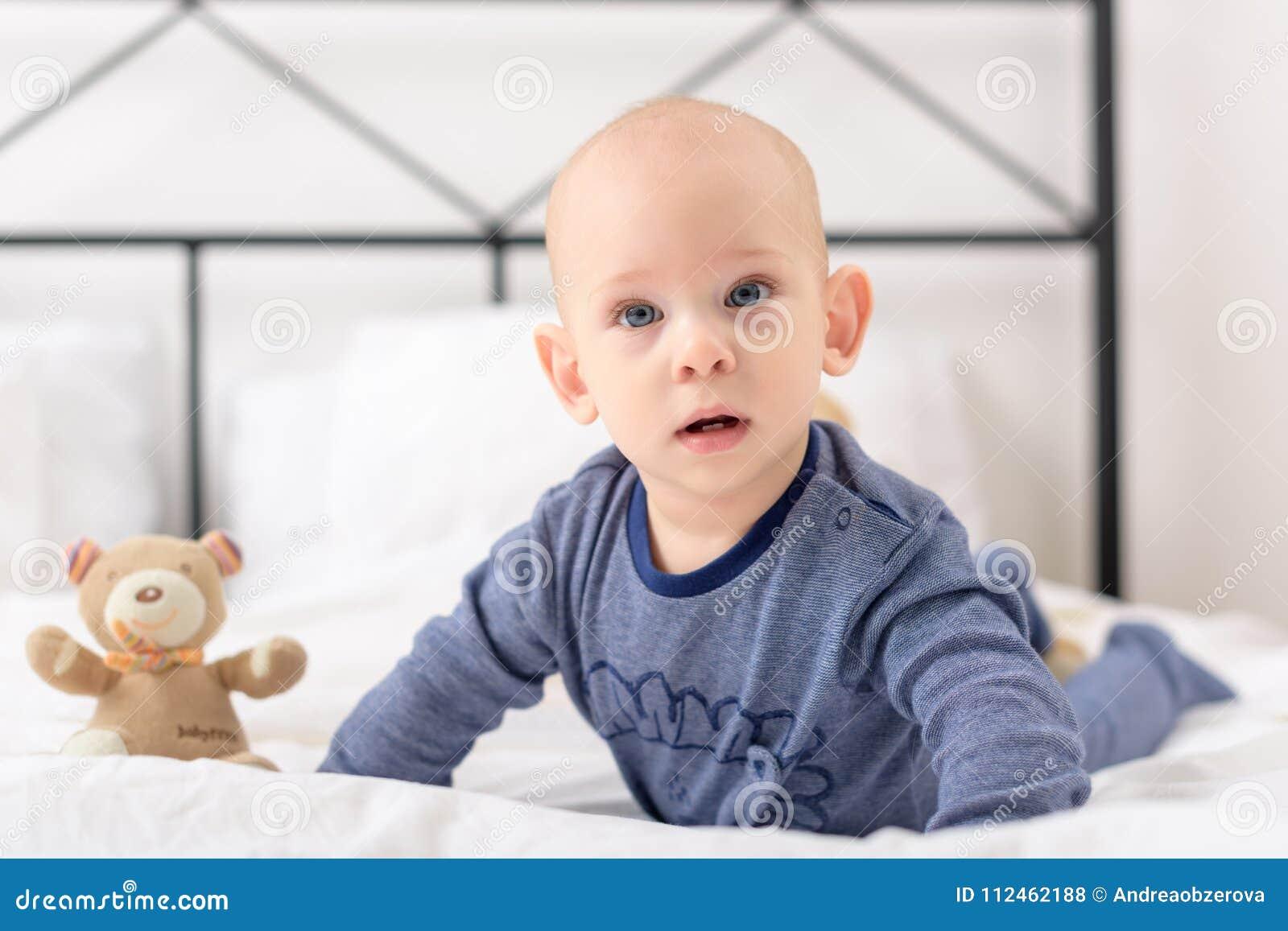 Il neonato adorabile che lplaying con il giocattolo riguarda un letto Rilassamento del bambino neonato