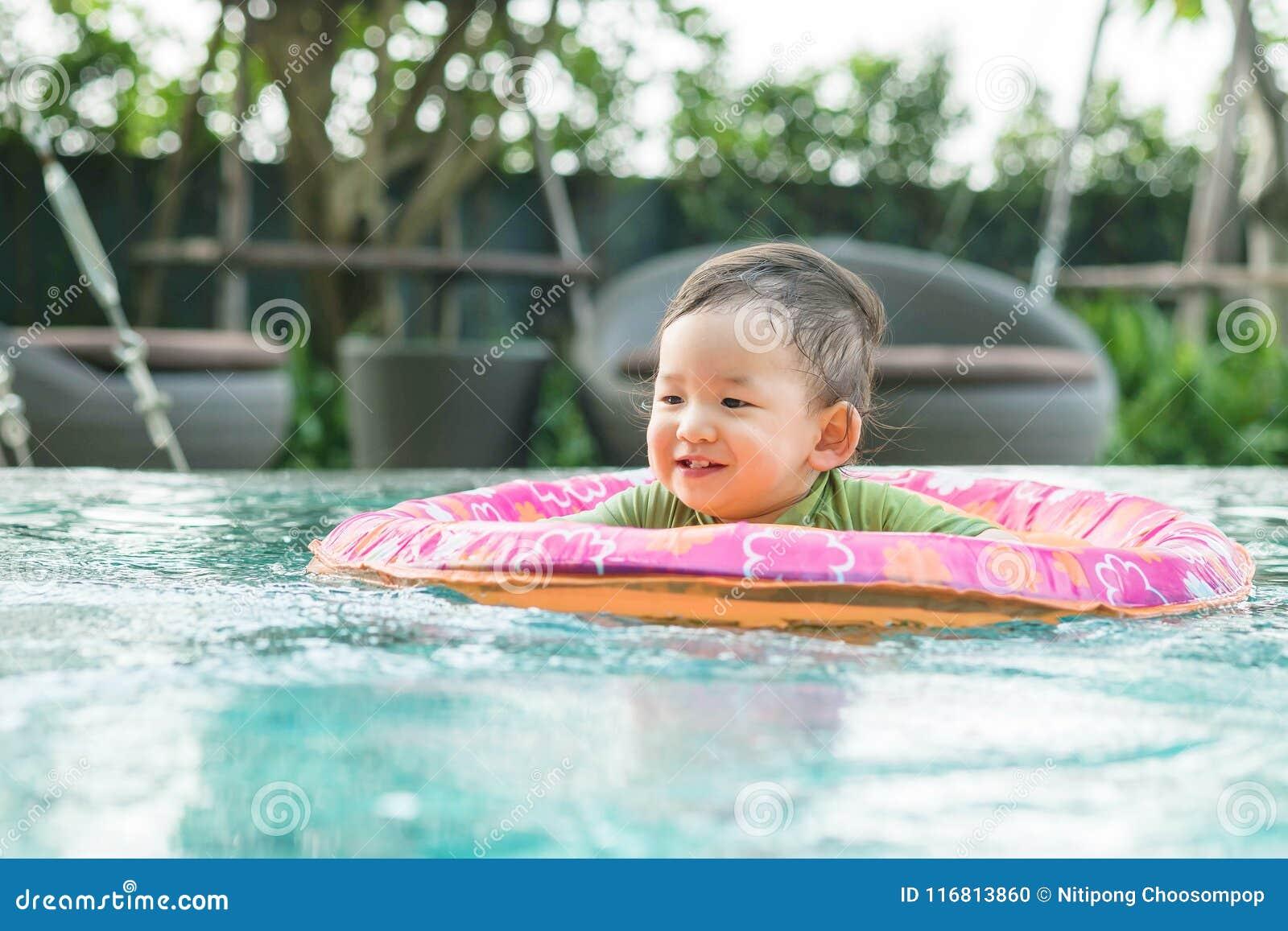 Il neonato asiatico del primo piano si siede in una barca per i bambini nei precedenti della piscina con il fronte di sorriso nel