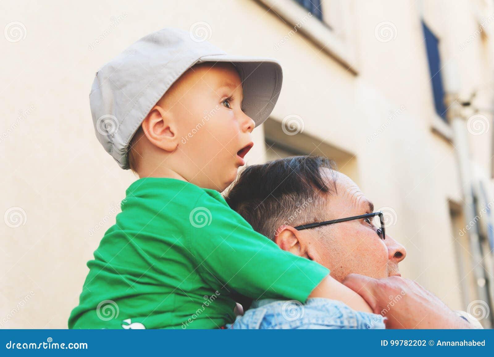 Il neonato sorpreso che si siede sul ` s del padre mette