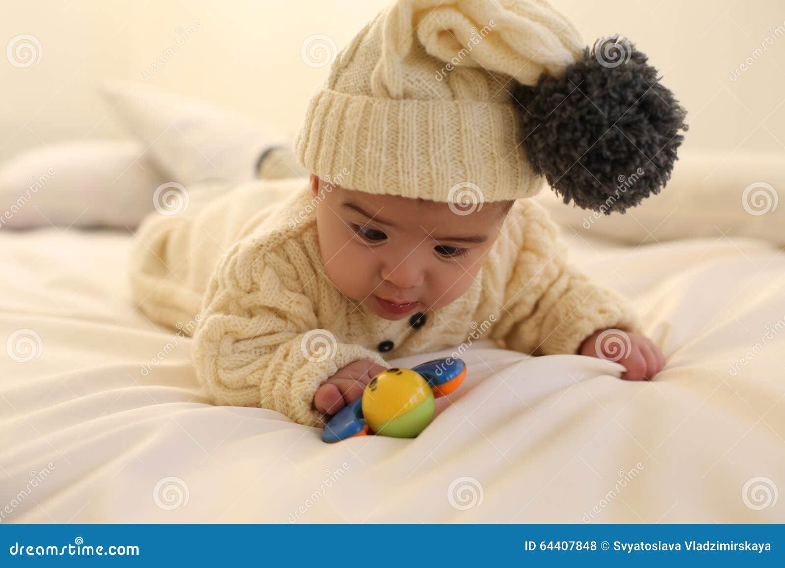 Il neonato sveglio, indossa i vestiti tricottati, giocanti con il giocattolo a casa accogliente