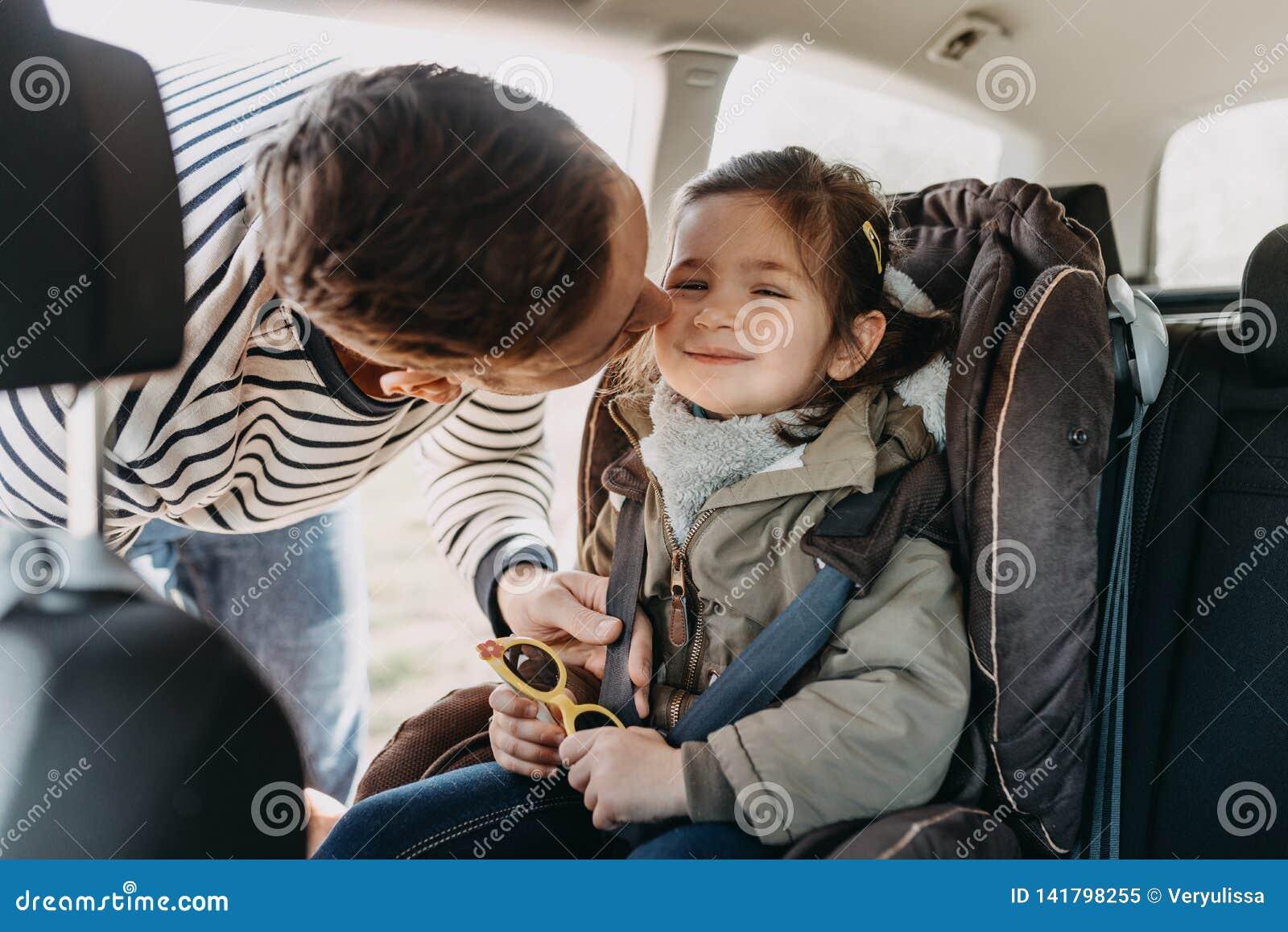 Il padre bacia sua figlia del bambino inarcata nella sua sede di automobile del bambino