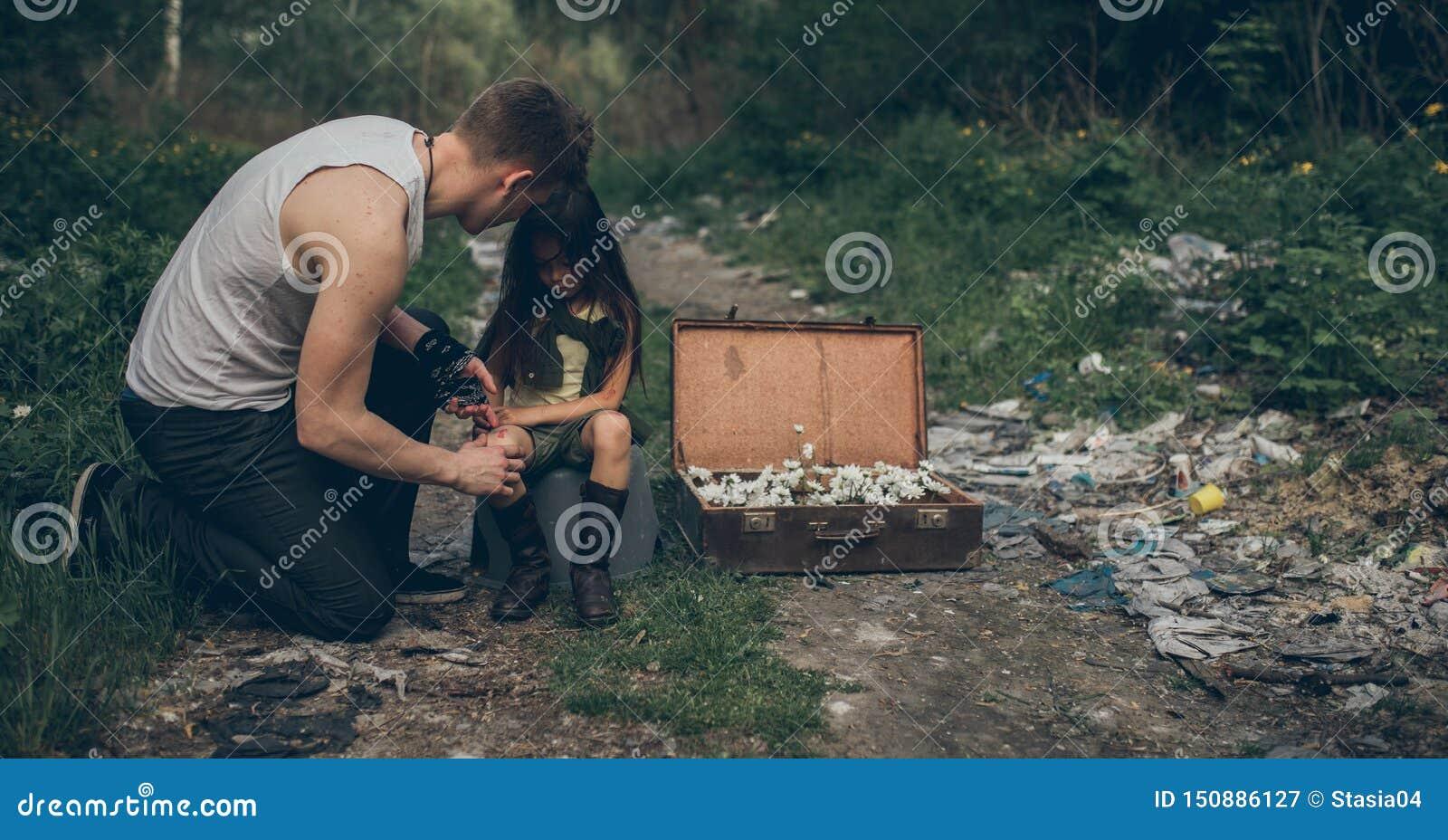Il padre e la figlia senza tetto sono nella discarica accanto ad una valigia con i fiori dentro