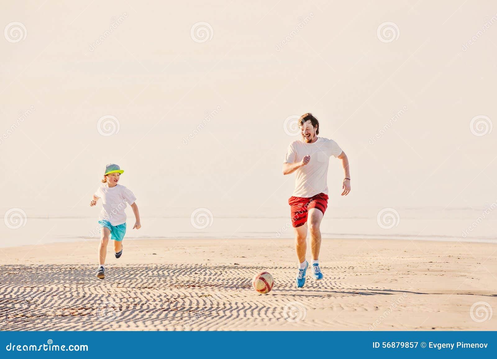 Il padre ed il figlio felici giocano a calcio o calcio sopra