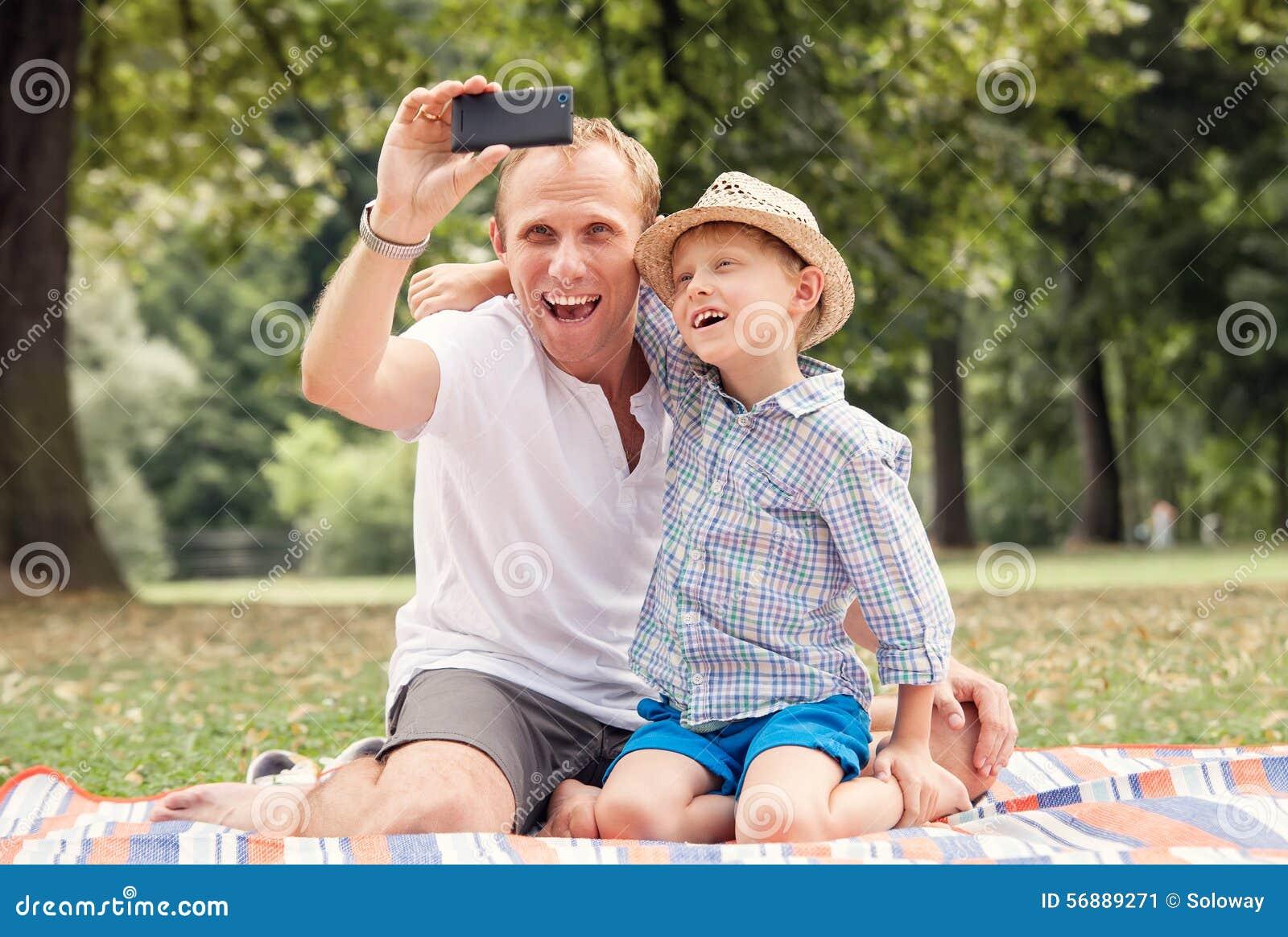 Il padre ed il figlio sorridenti felici prendono un immagine di auto con un telefono