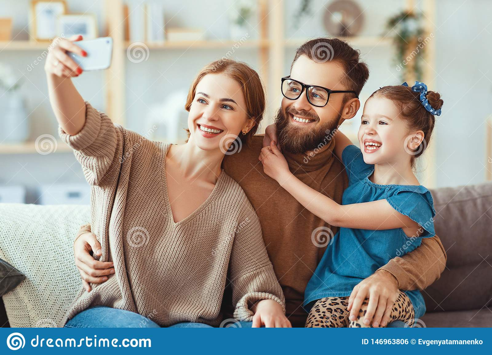 Il padre felice allegro ed il bambino della madre della famiglia prendono i selfies, prendono le immagini