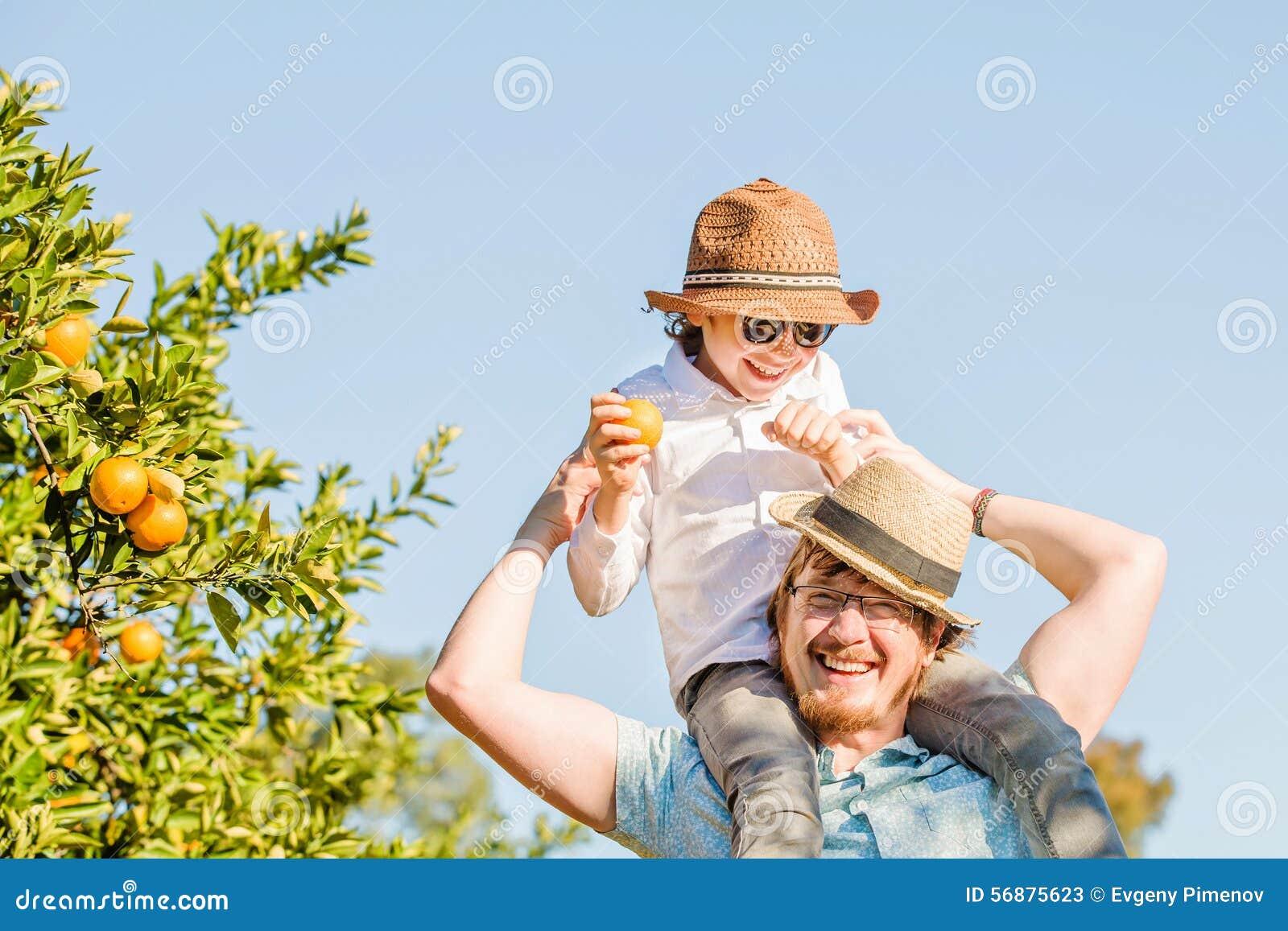 Il padre felice con il suo giovane figlio si diverte sull agrume