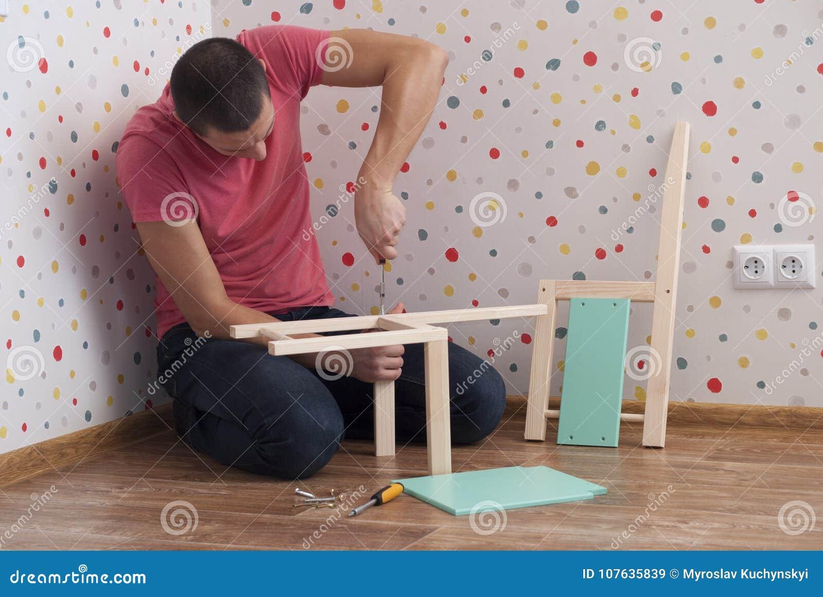 Il padre monta una sedia per i bambini