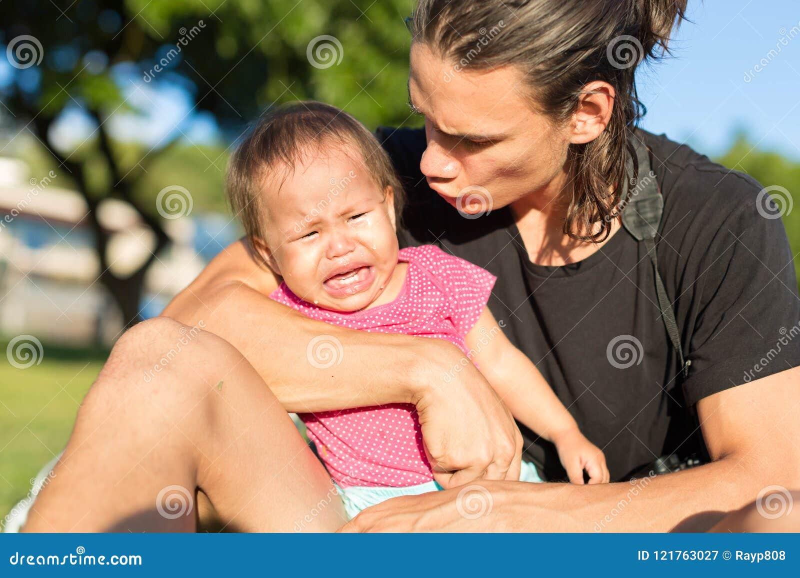 Il padre sottolineato e frustrato prova a confortare sua figlia del bambino di ribaltamento dal gridare in una regolazione del pa