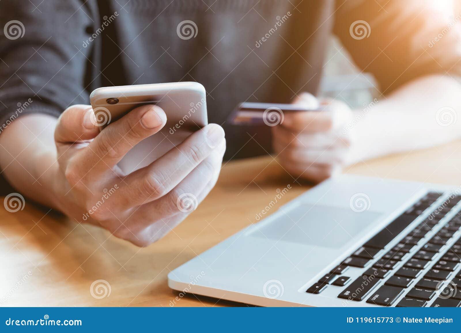 Il pagamento online, il ` s dell uomo passa lo smartphone della tenuta e credito c usando