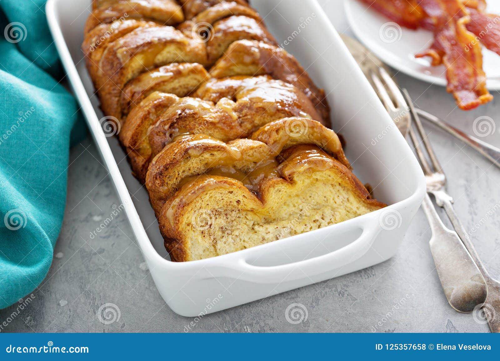 Il pane inzuppato in latte/uova e zucchero e fritto in padella cuoce in un piatto bianco