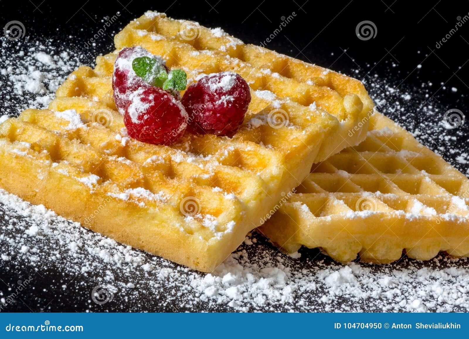 Il pane tostato dolce waffles con i lamponi e un ramoscello della macro del primo piano della polvere delle foglie e dello zucche
