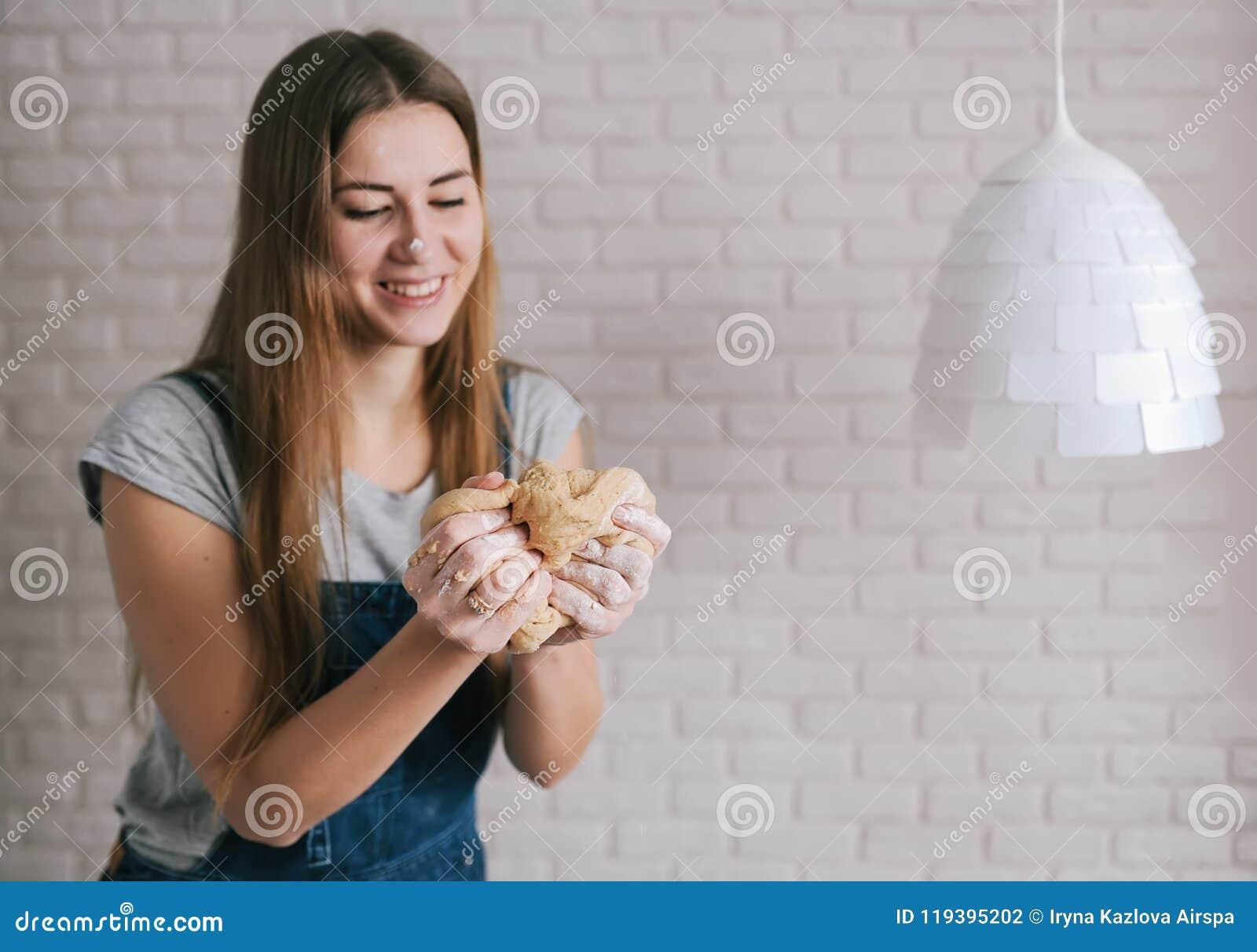Il panettiere felice della donna impasta il grumo della pasta contro lo sfondo di un muro di mattoni e della lampada bianca