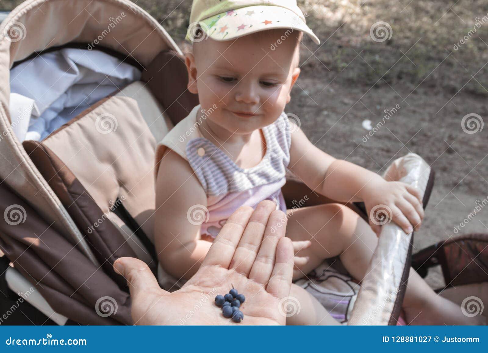 Il papà offre le bacche selvatiche al bambino, fresco, sano e pieno delle vitamine