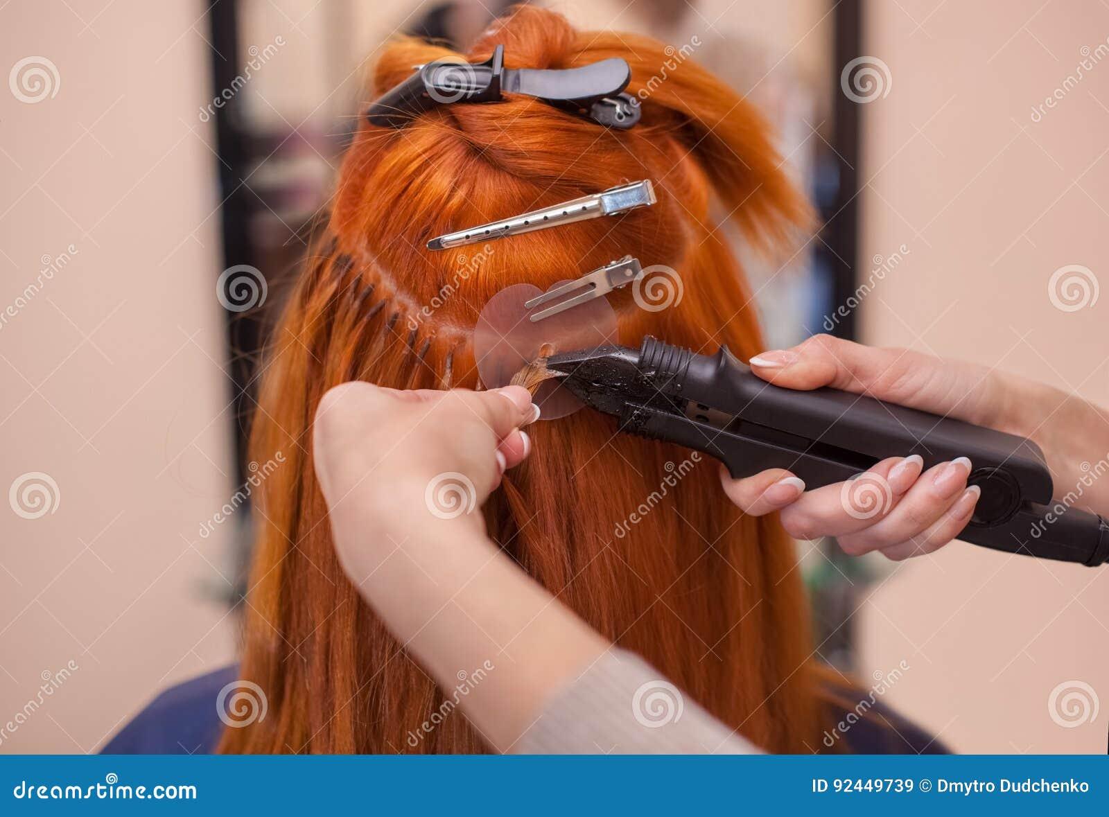 Il parrucchiere fa le estensioni dei capelli ad una giovane, ragazza dai capelli rossi