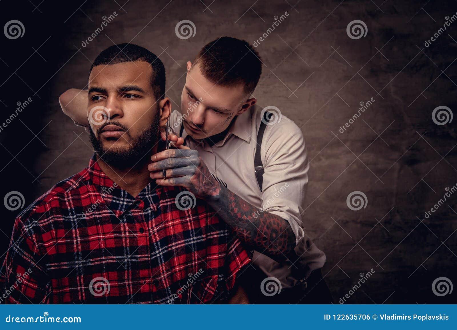 Il parrucchiere tatuato professionista antiquato fa un taglio di capelli ad un cliente afroamericano su buio strutturato