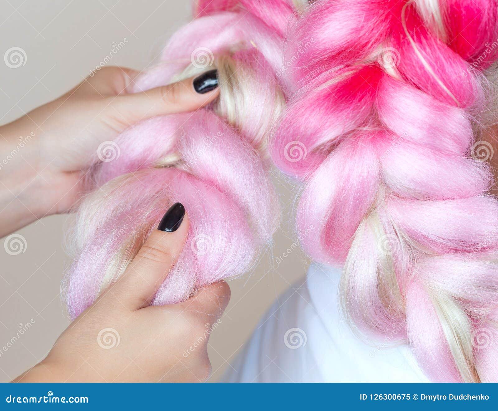 Il parrucchiere tesse le trecce con la bella bionda dei kanekalons rosa