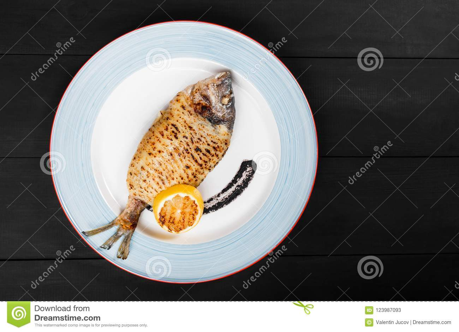 Il pesce arrostito di dorado con il limone ed il tartufo sauce sul piatto su fondo di legno