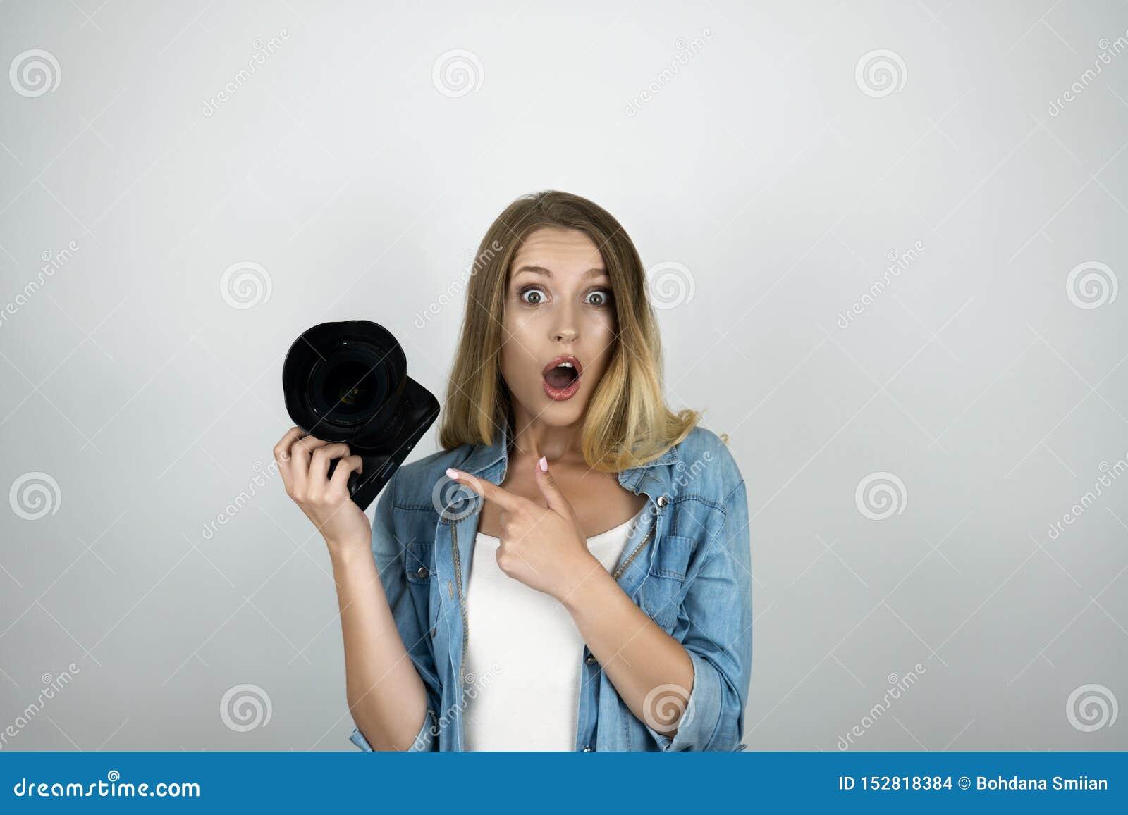Il photocamera biondo felice della tenuta della giovane donna nei suoi sguardi della mano ha sorpreso indicare al suo fondo bianc