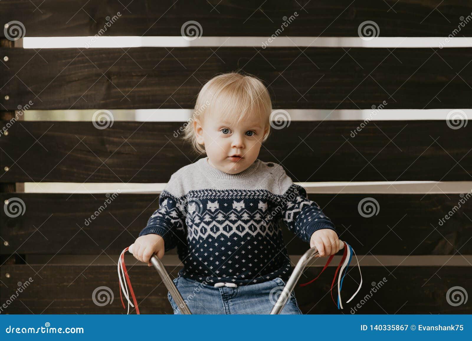 Il piccolo bambino biondo sveglio adorabile prezioso del ragazzo del bambino del bambino che gioca fuori su Toy Bicycle Scooter M