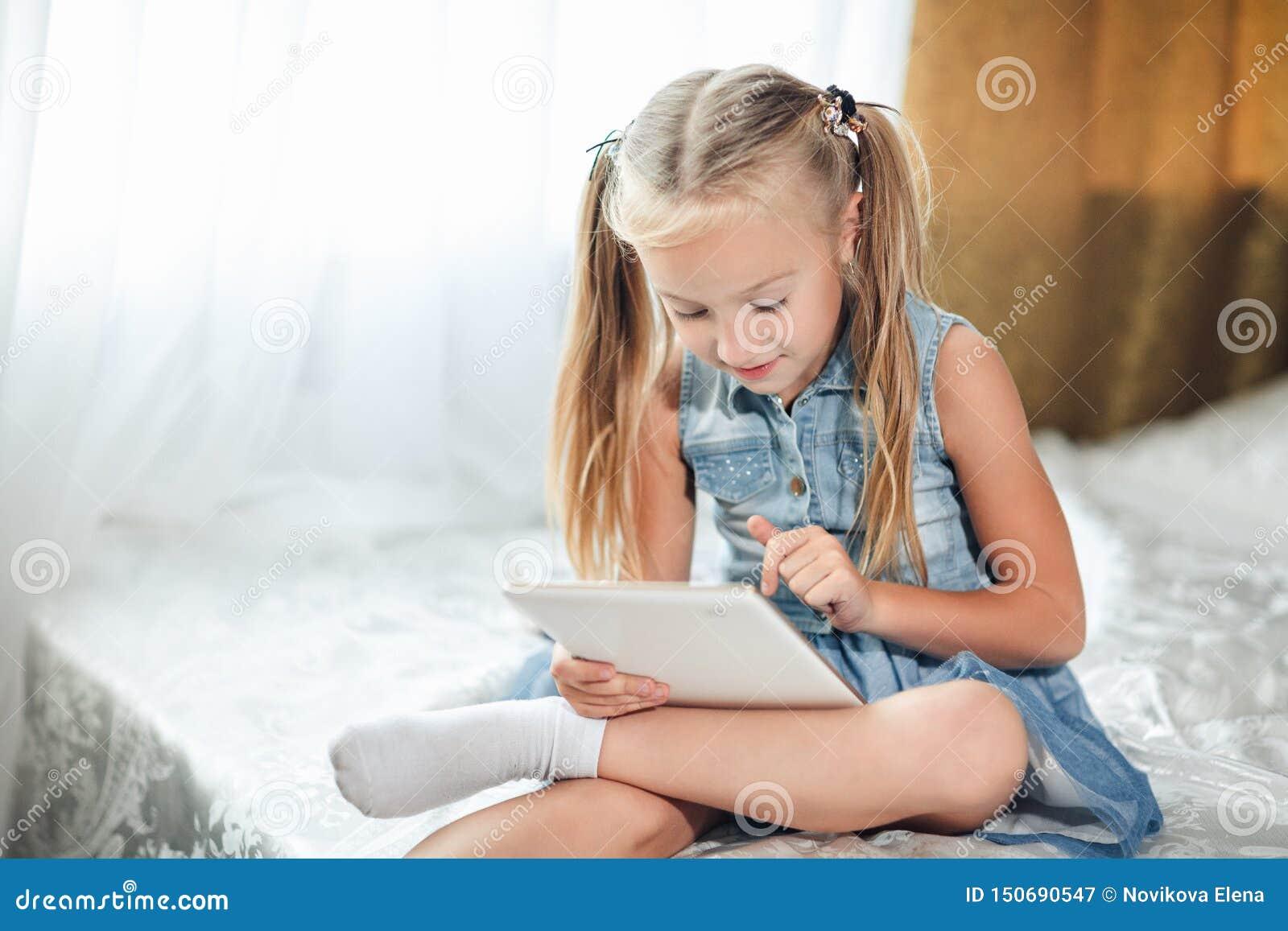 Il piccolo bambino che sveglio la ragazza bionda in prendisole del denim si trova a letto utilizza la compressa digitale Bambino