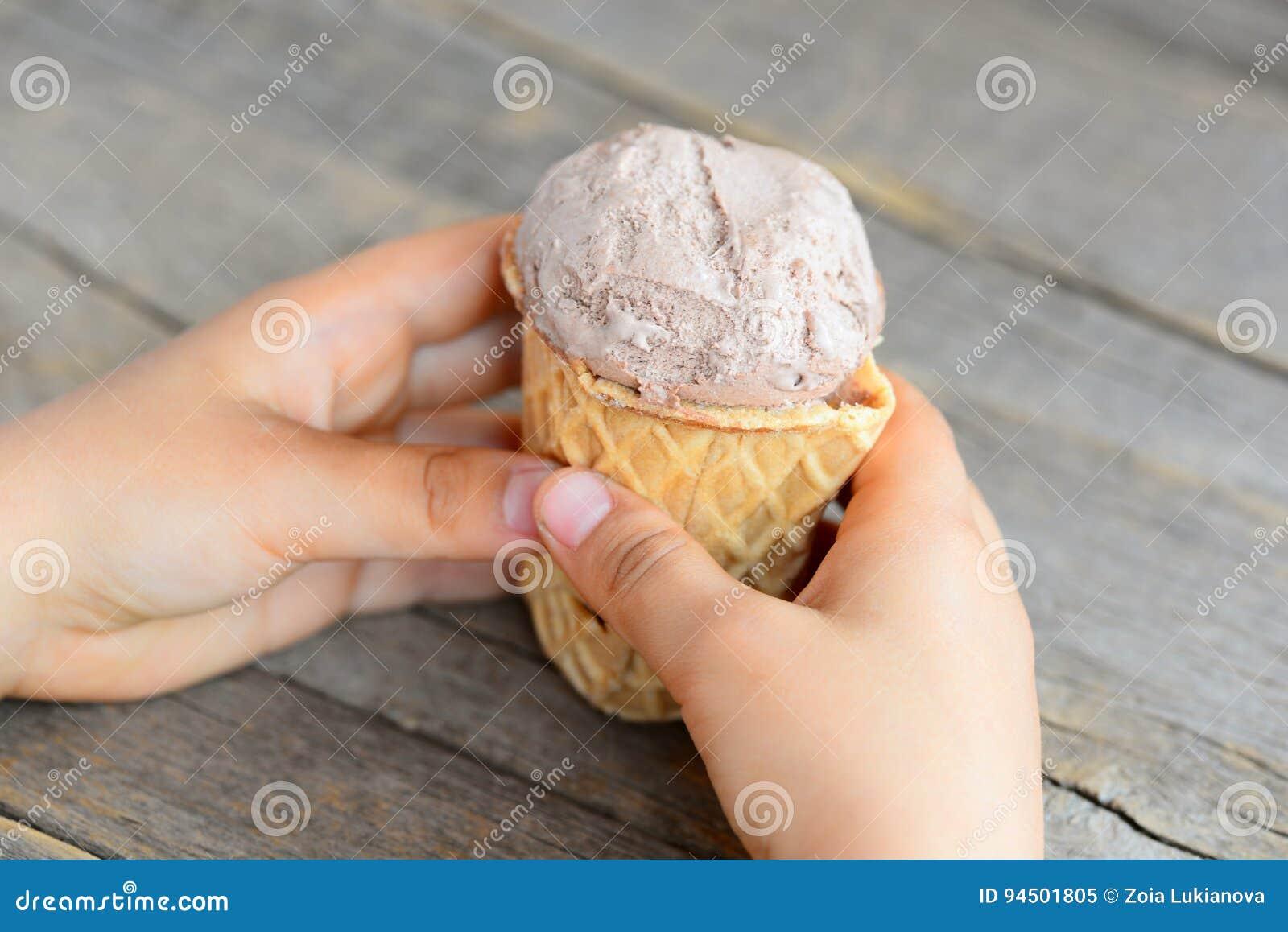 Il piccolo bambino tiene un gelato in sua mano Piccolo bambino che mangia un gelato in una tazza della cialda Vecchia priorità ba