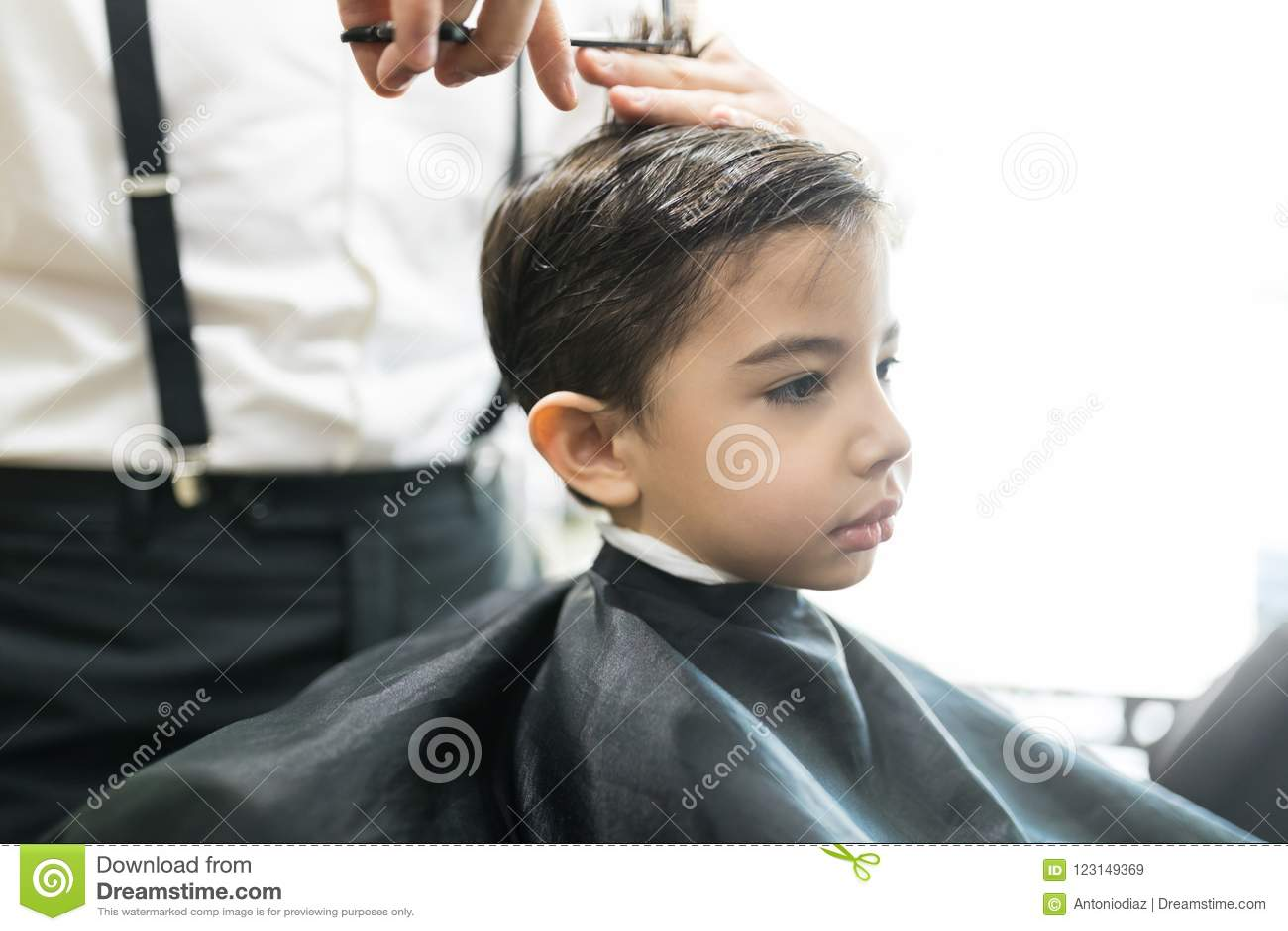 Il piccolo cliente sta ottenendo il taglio di capelli dal parrucchiere At Barber Shop