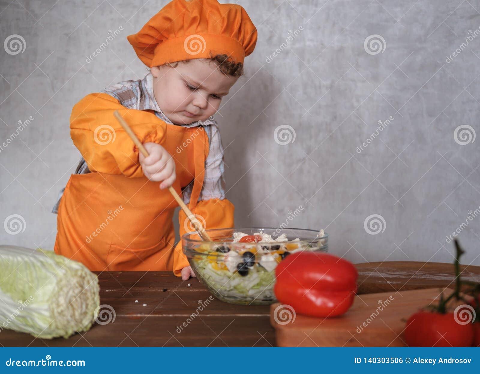Il piccolo ragazzo europeo divertente vestito come un cuoco unico mescola un insalata greca con un cucchiaio