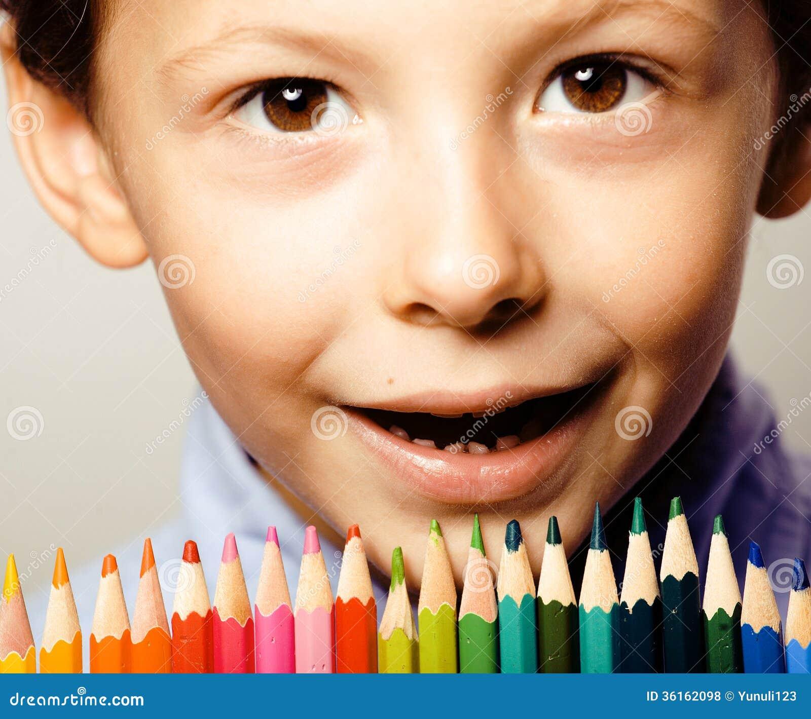 Il piccolo ragazzo sveglio con le matite di colore si chiude sul sorridere