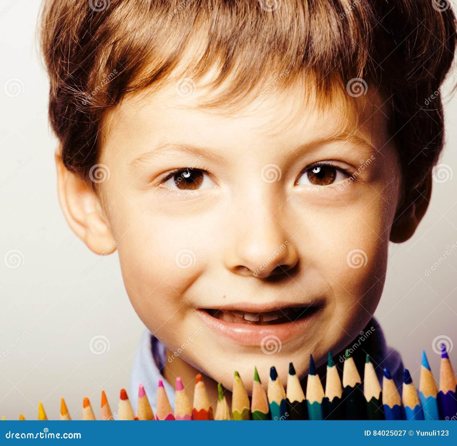Il piccolo ragazzo sveglio con le matite di colore si chiude sul sorridere, l istruzione f