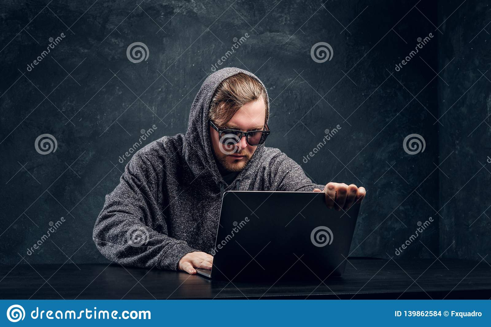 Il pirata informatico barbuto in maglione grigio ed occhiali da sole si siede alla tavola nera