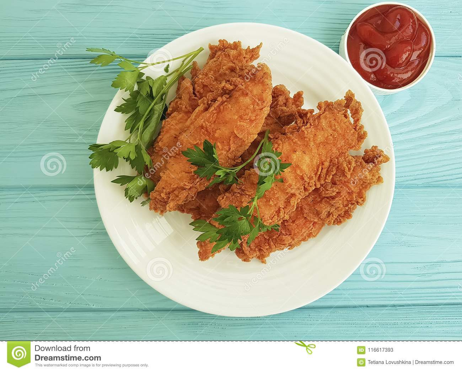 Il pollo fritto ha fritto la cena deliziosa nell impanare, prezzemolo, ketchup del pranzo su di legno blu