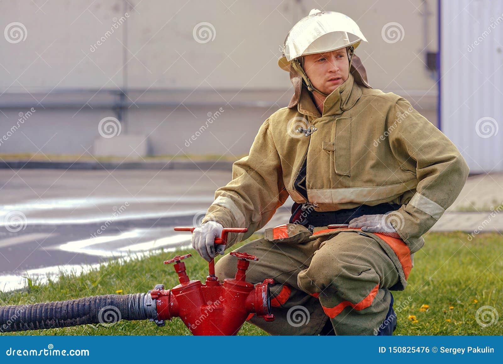 Il pompiere svita la valvola dell idrante per fornire l acqua tramite il tubo flessibile Ritratto del bagnino maschio bianco in v