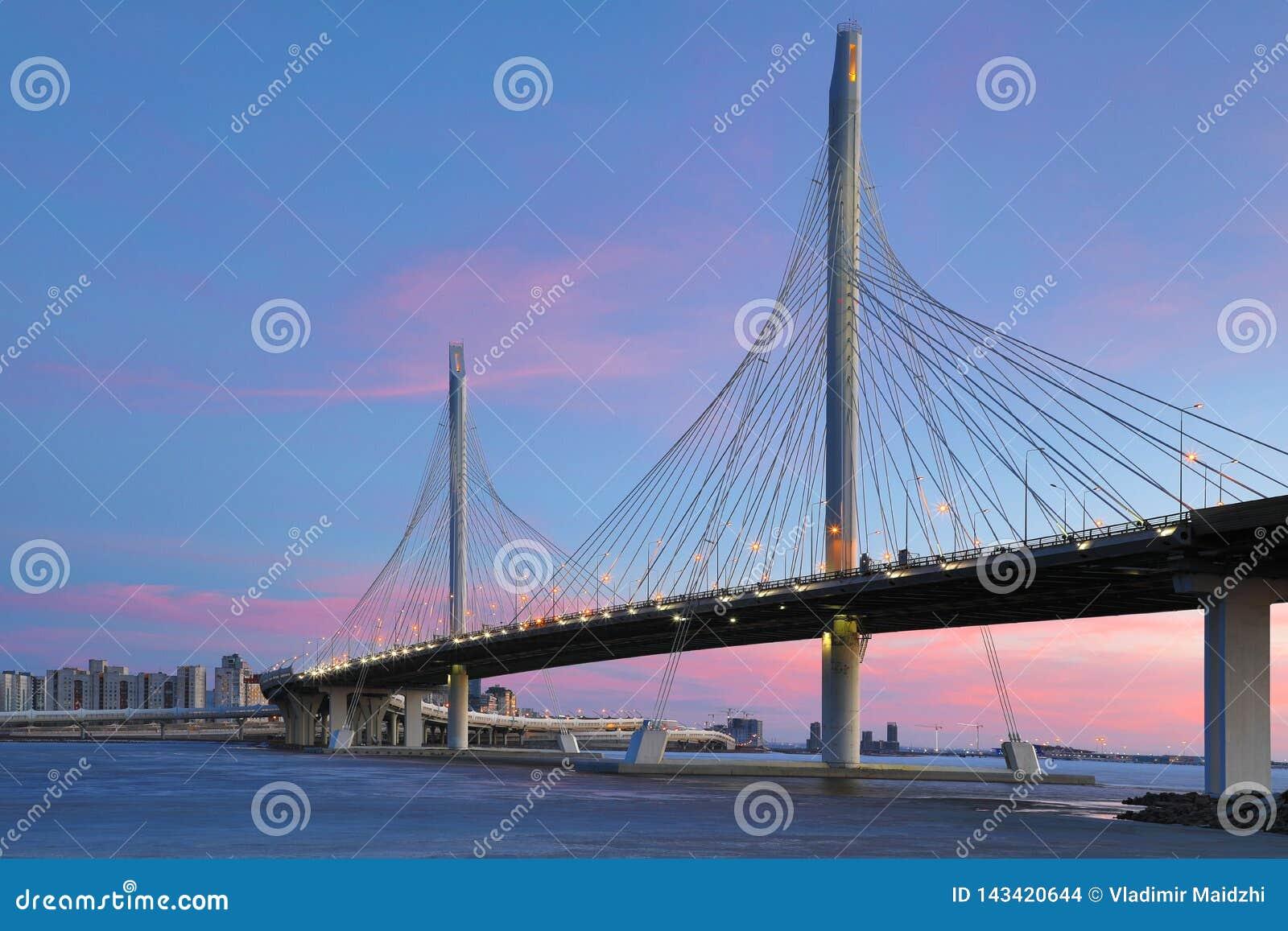 Il ponte della strada della strada principale del cerchio sopra il fiume di Neva vicino alla bocca di nell ora blu dopo il tramon