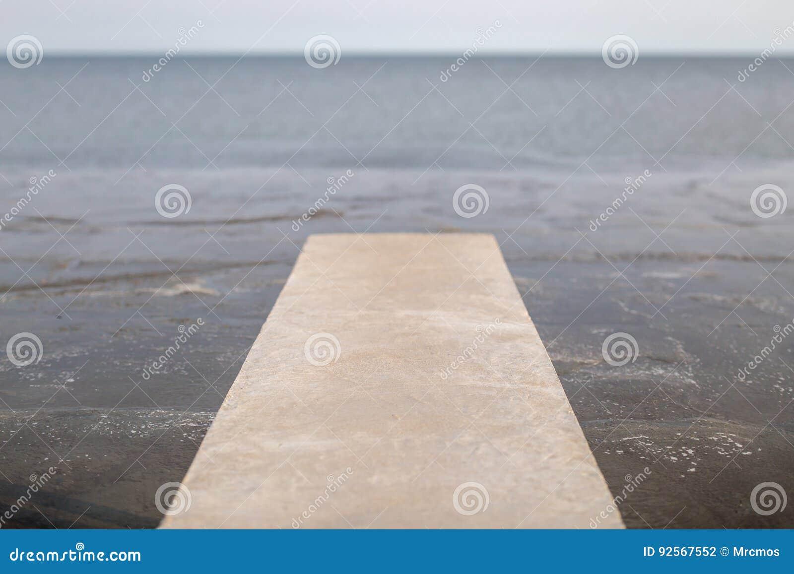 Il ponte lungo vago del cemento della foto estendere al mare con naturale