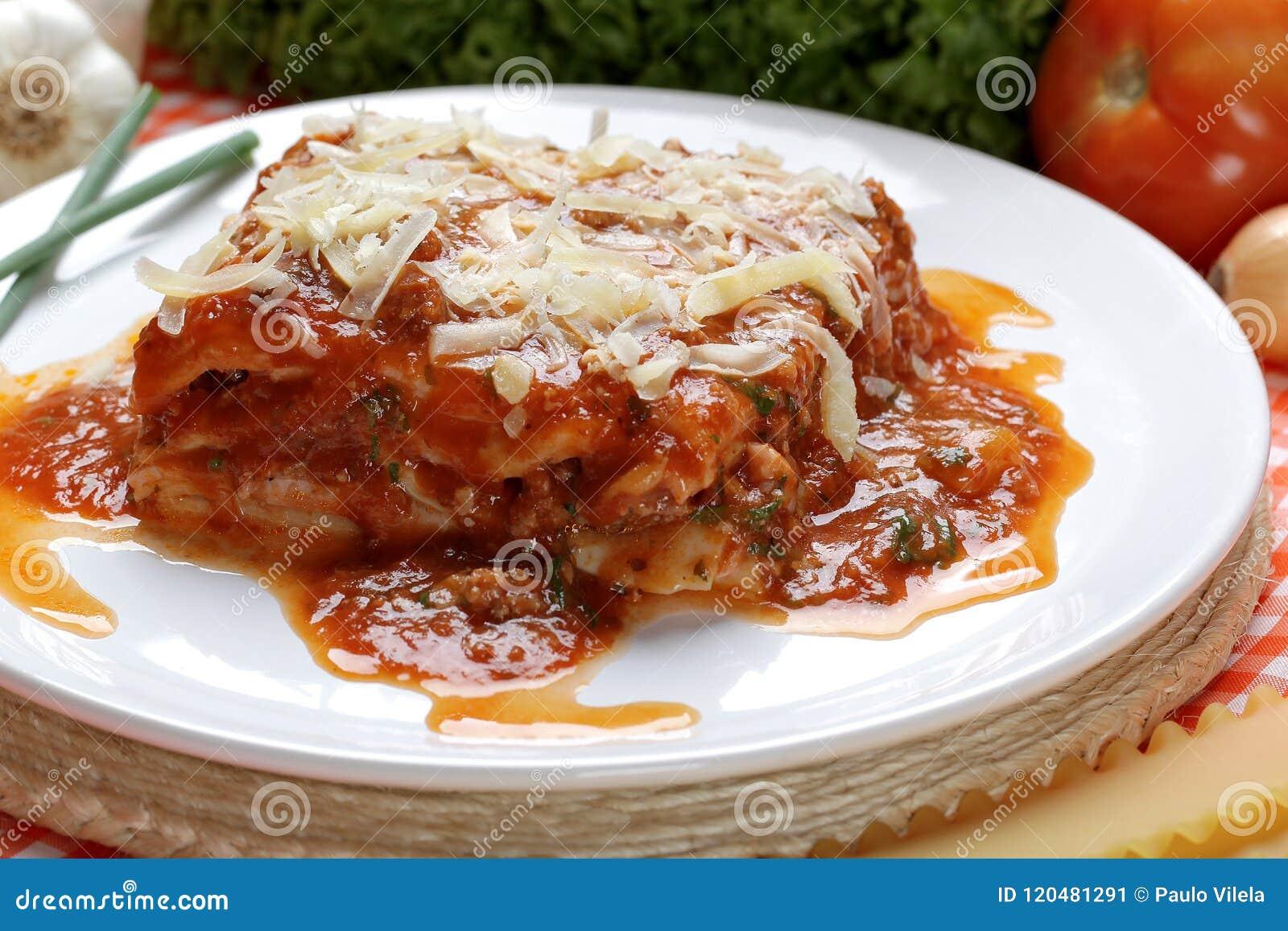 Il primo piano delle lasagne al forno tradizionali fatte con la salsa bolognese del manzo tritato completata con le foglie del ba