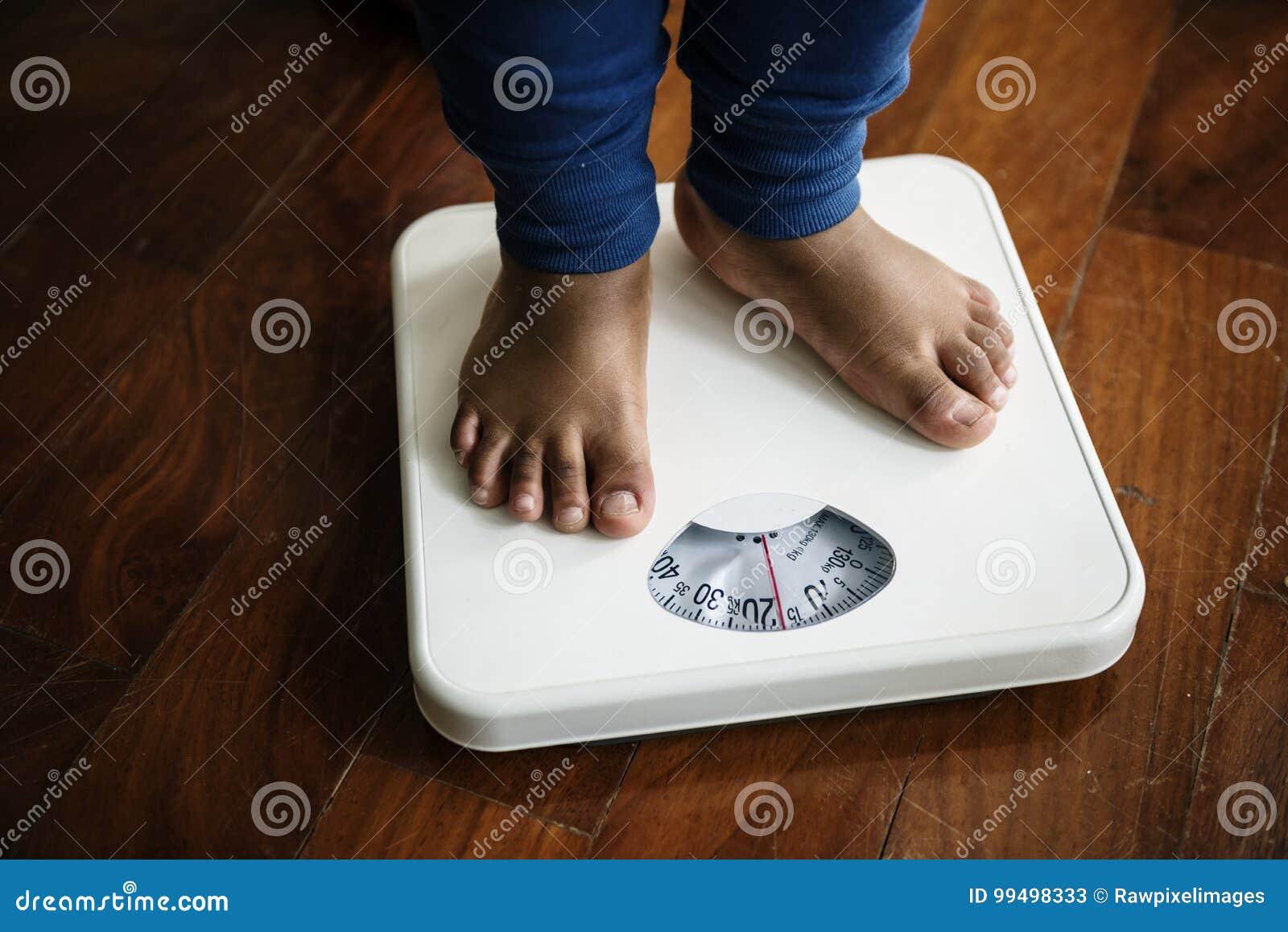 Il primo piano di un paio della gamba che misura sopra pesa la scala