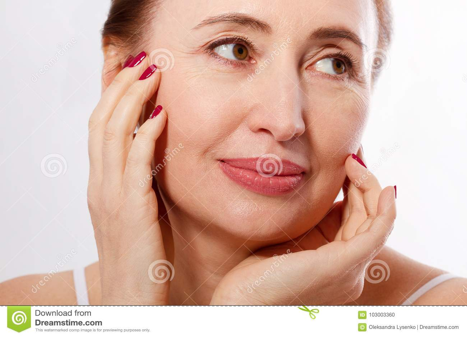 Il primo piano ed il ritratto di macro di bello e mezzo sano hanno invecchiato il fronte della donna su fondo bianco Grinze e men
