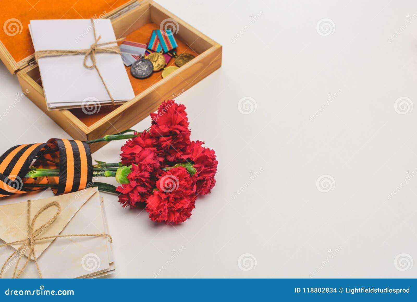 Il primo piano ha sparato della scatola con le medaglie, pile di lettere, garofani avvolti dal nastro di St George su gray, conce